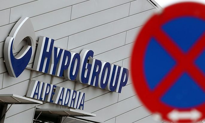 The logo of Hypo Alpe Adria is pictured behind a traffic sign at the bank's headquarters in Klagenfurt
