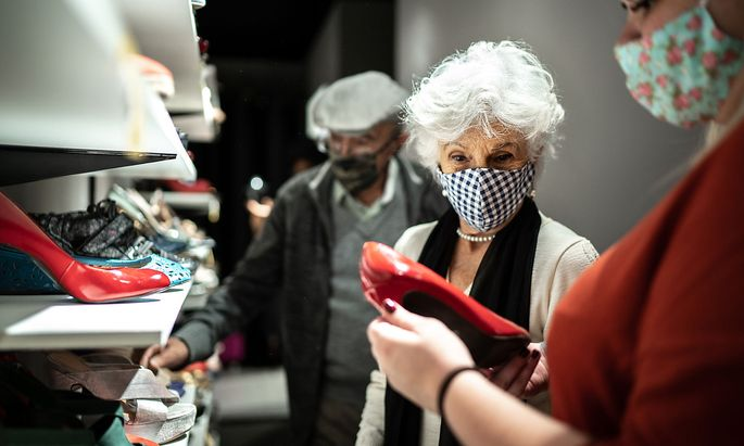 Senior couple wearing face mask being helped by a saleswoman while shopping for shoes in a thrift store