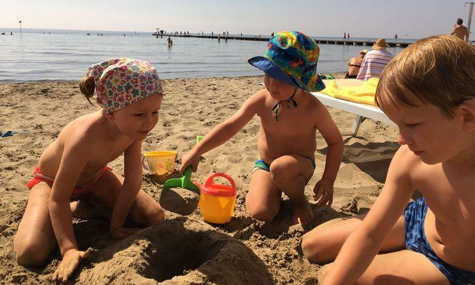 Paul (7) mit seinen Geschwistern, Clara und Karl, beim Sandburgenbauen in Grado.