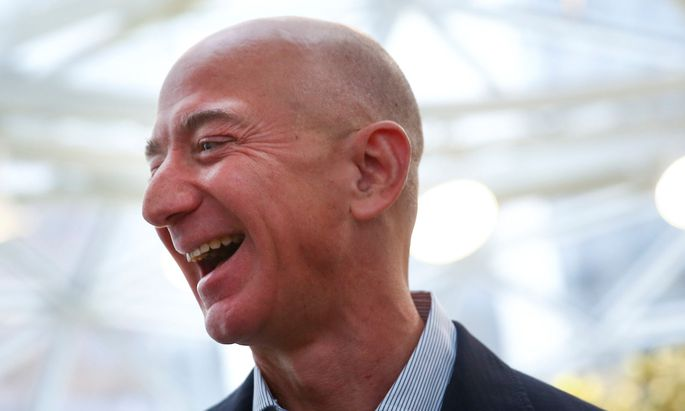 Amazon founder and CEO Jeff Bezos laughs as he talks to the media while touring the new Amazon Spheres during the grand opening in Seattle