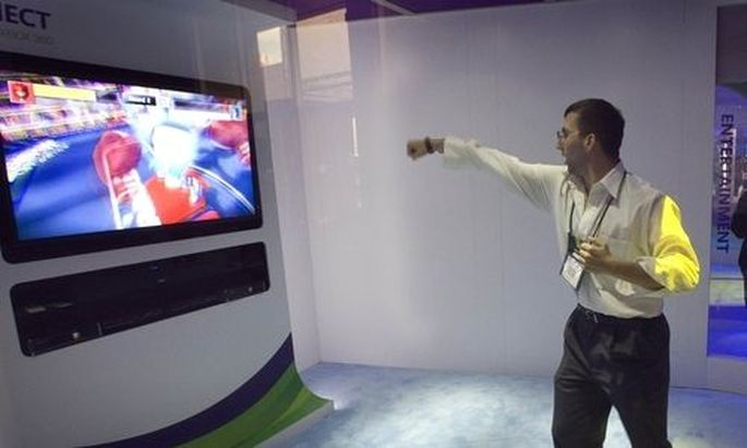 A man plays a Kinect for XBox 360 boxing game at the Microsoft booth during the 2011 International Co