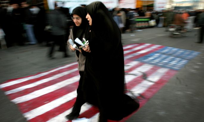 FILE PHOTO: Iranian women walk on a U.S. flag during a demonstration to mark the 27th anniversary of Iran´s Islamic Revolution in Tehran