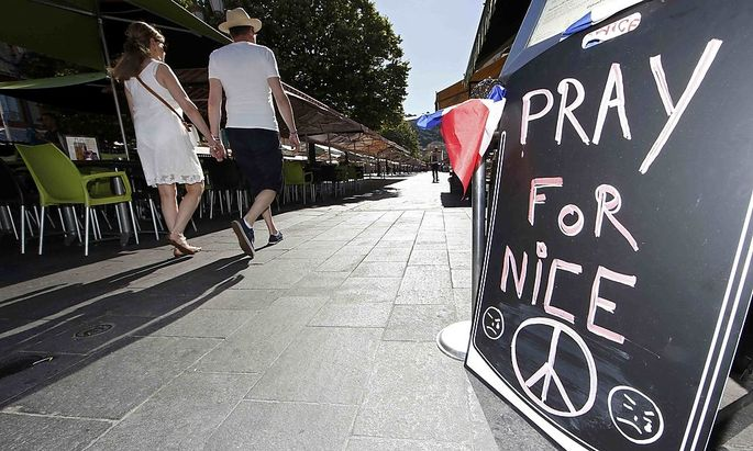 A couple walk through the empty flower market in the old city and near a sign which reads, 'Pray for Nice' days after a truck attack on the Promenade des Anglais on Bastille Day killed scores and injured as many in Nice