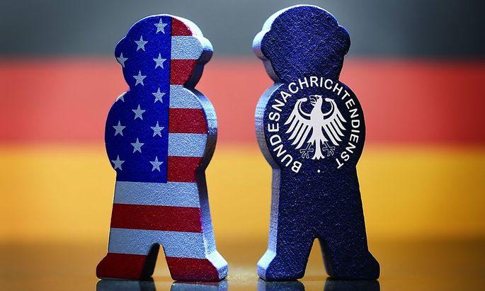Figur mit Zeichen des BND und mit US-Nationalfarben vor deutscher Fahne
