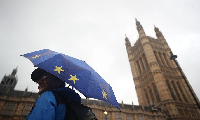 An anti-Brexit protester shelters under an EU flag themed umbrella opposite the Houses of Parliament in London