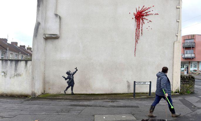 Ein Mädchen mit einer Steinschleuder in der Hand, darüber ein riesiger roter Klecks - von Banksy?