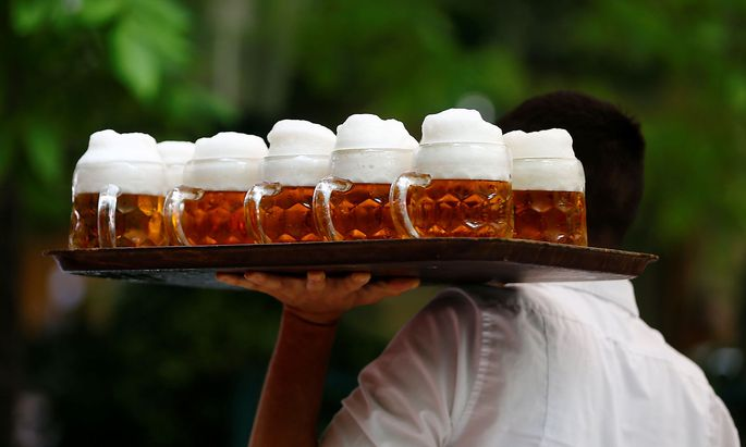 A waiter serves beer in the traditional Schweizerhaus beer garden in Vienna