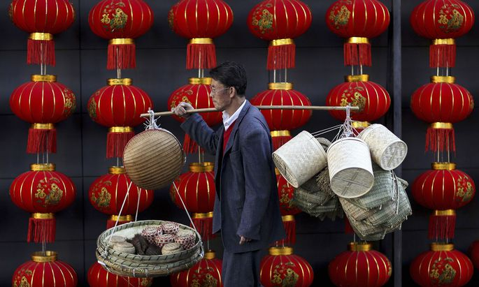 File photo of a basket vendor walking past red lanterns serving as decorations to celebrate the new year outside a shopping mall in Kunming