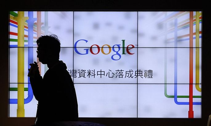 A man walks past a TV wall during a media tour at the Google data centre in central Taiwan
