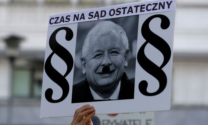 A protester holds a poster with a picture of Law and Justice party leader Jaroslaw Kaczynski and the words 'It is time for the Judgement Day' during an anti-government protest in support of free courts in front of the the Senate building in Warsaw