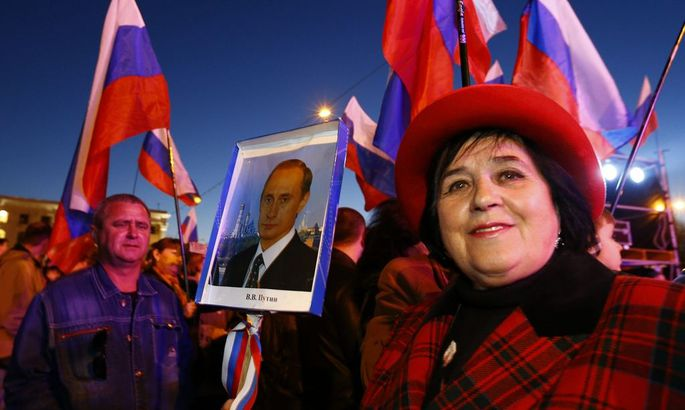A woman holds a portrait of Russia's President Vladimir Putin during celebrations on the main square of the Crimean city of Simferopol