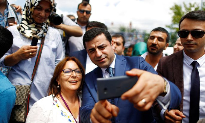 The leader of Turkey's pro-Kurdish opposition Peoples' Democratic Party Demirtas, takes a selfie with supporters during a rally in Istanbul