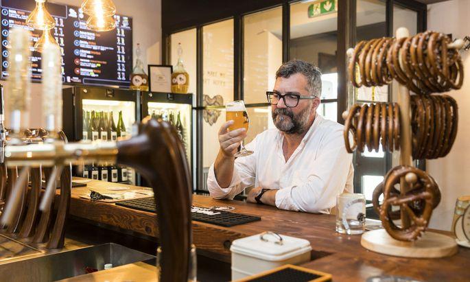 """Friedrich Moser an der Bar des Ammutsøn in Wien Mariahilf – in dem auch sein Film beginnt. Das Bier ist von """"Bierol""""."""