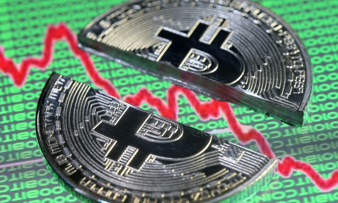 Broken representation of the Bitcoin virtual currency, placed on a monitor that displays stock graph and binary codes, are seen in this illustration picture