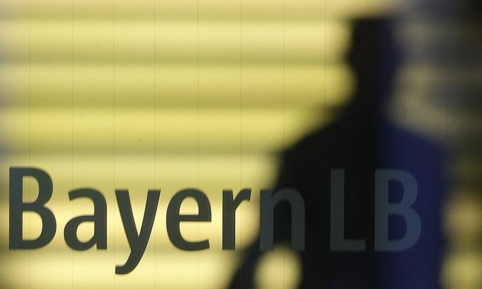 File photo of an employee of the Bavarian public sector bank BayernLB walking near the bank's logo in Munich