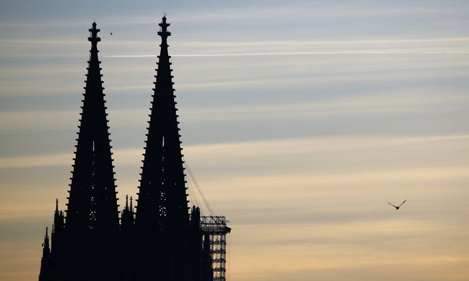 A bird flies next to the two towers of the famous landmark and UNESCO world heritage, the Cologne Cathedral