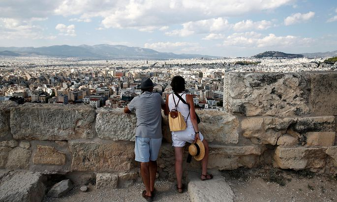 Tourists enjoy the view from the Acropolis hill in Athens