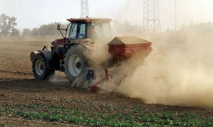 Traktor auf einem Feld verstreut Glyphosatzur Unkrautbek�mpfung McPBBO *** Tractor in a field sca