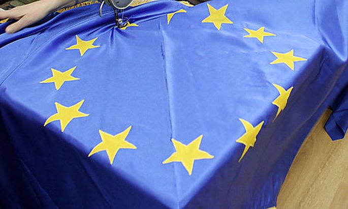 FILE - In this file photo taken on Dec. 19, 2005, a seamstress sews an EU flag in a Belgrade workshop