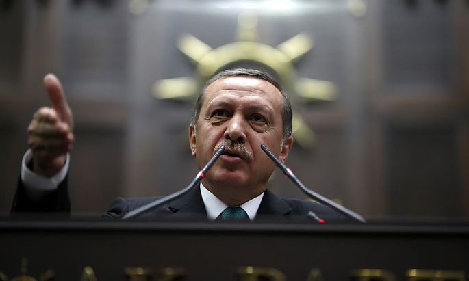 Turkey's Prime Minister Erdogan addresses members of parliament from his ruling AK Party during a meeting at the Turkish parliament in Ankara