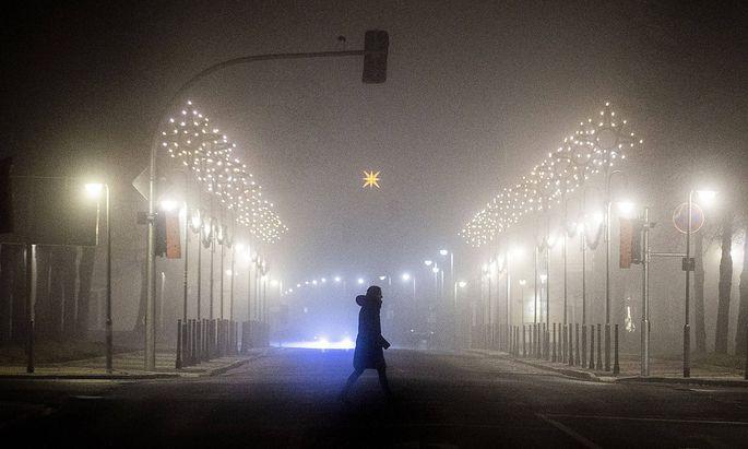 Eine Frau laeuft entlang einer mit Weihnachtsbeleuchtung geschmueckten Strasse im Nebel in Niesky, 11.12.2020. Die saech
