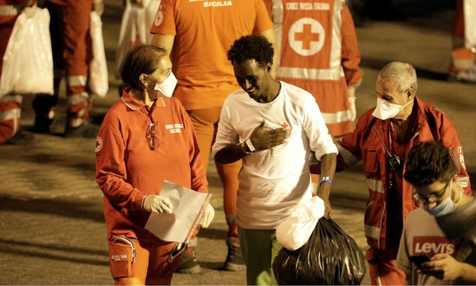 A migrant is helped by Red Cross memebrs after disembarking from Italian coast guard vessel ´Diciotti´ at the port of Catania