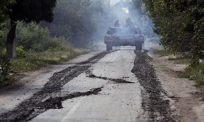 A Ukrainian tank moves along a road near Eastern Ukrainian village of Novoselivka Persha