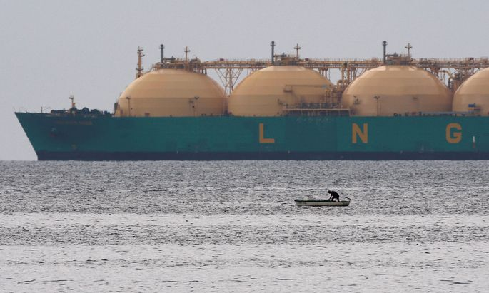 FILE PHOTO: Fisherman stands in boat as a liquid natural gas tanker passes the coast near Havana