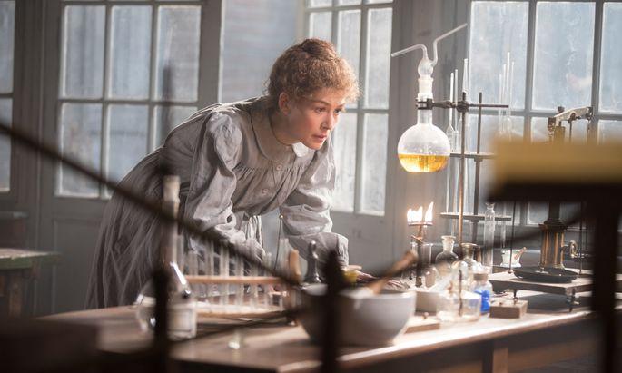 Rosamund Pike gibt Marie Curie mit dem Stolz einer Besessenen, die noch nicht weiß, dass ihre eigene Entdeckung ihren Körper zerstören wird.