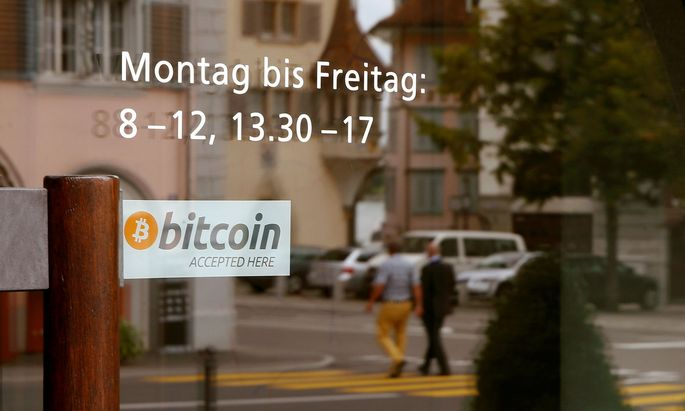 A sticker reading 'Bitcoin accepted here' is displayed at the entrance of the Stadthaus town hall in Zug