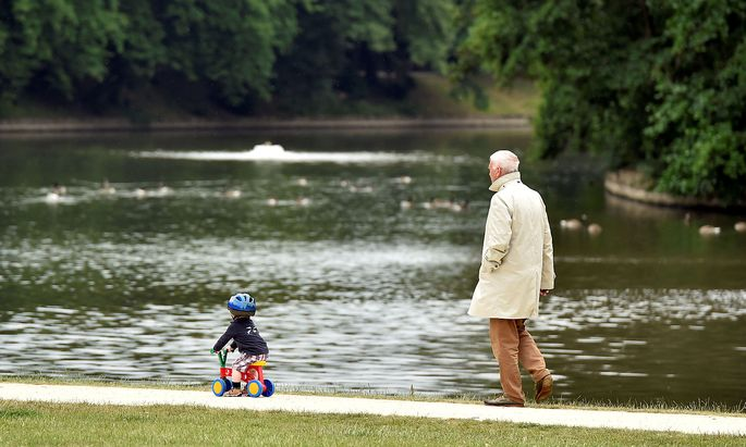 A man walks behind a boy in a park in Brussels