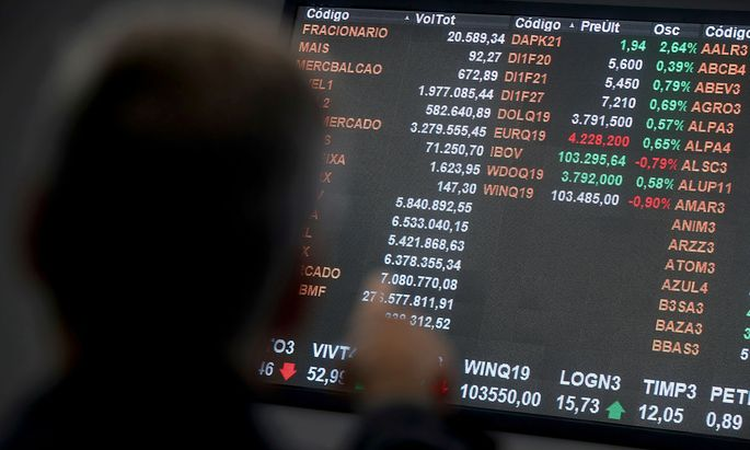 FILE PHOTO: Currency exchange rates of euro and the U.S. dollar are seen on an electronic board as a man points at it on the floor of Brazil's B3 Stock Exchange in Sao Paulo