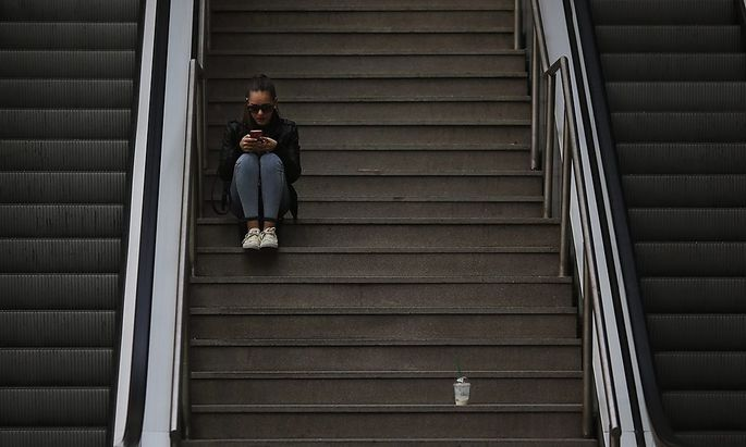 A woman uses her mobile phone as she sits on the stairs at Principe Pio station in Madrid