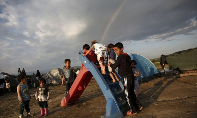 Children play on a slide as a rainbow forms overhead at a makeshift camp for refugees and migrants near the village of Idomeni