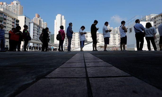 Lange Schlangen vor den Wahllokalen in der Finanzmetropole: Bei der Abstimmung in Hongkong zeichnete sich eine Rekordbeteiligung ab.