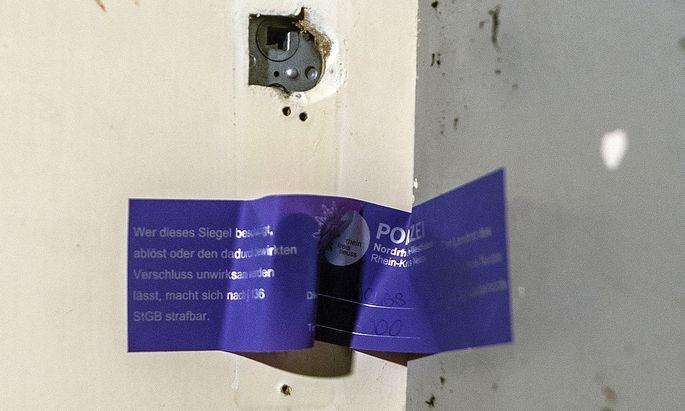 Ein Polizeisiegel an der Wohnungstür des mutmaßlichen Komplizen in Neuss.