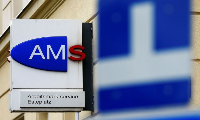 The logo of AMS jobcentre is seen behind traffic signs in Vienna