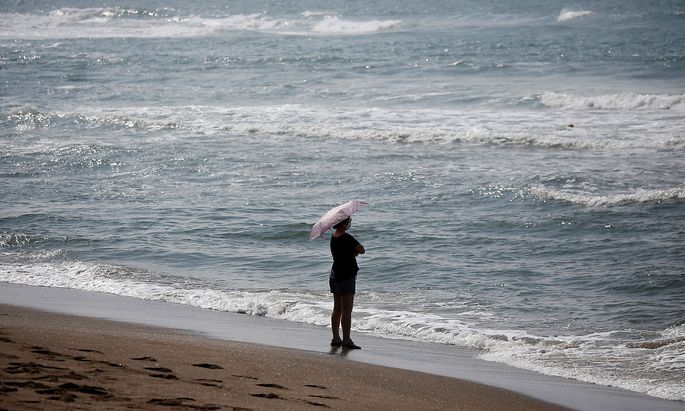 A woman wearing a mask enjoys a late summer day amid the coronavirus disease (COVID-19) outbreak on Jeju island