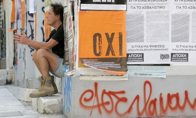 A man sits on a building entrance, next to a referendum campaign poster with the word 'No' in Greek in Athens