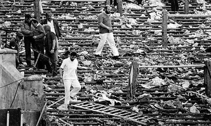 FILE - In this May 29, 1985 file photo, spectators walk through the personal belongings of victims li