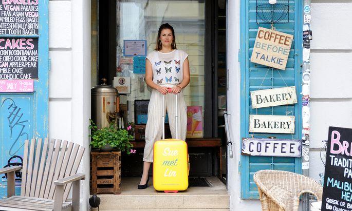 Marisa Mühlböck ist selbst eine geübte Alleinreiserin. Sie will mit Sue met Lin (siehe Logo auf dem Koffer) alleinreisende Frauen untereinander vernetzen. Das Foto entstand in der Pure Living Bakery in Wien Neubau.