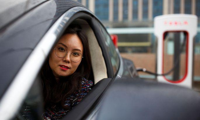 Archivbild: Eine Tesla-Fahrerin bei einer Ladestation in Peking