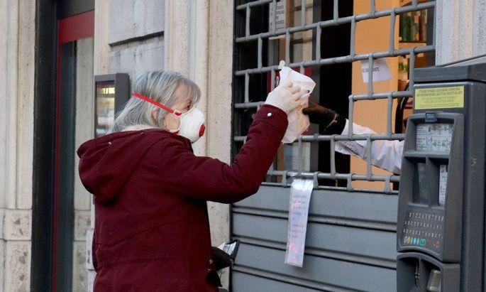 Italienerin mit Schutzmaske bei der Apotheke.