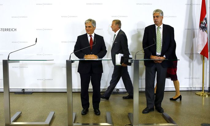 Austrian Vice Chancellor and Economics Minister Mitterlehner walks to join Chancellor Faymann and Finance Minister Schelling as they address a news conference after a government conclave in Schladming
