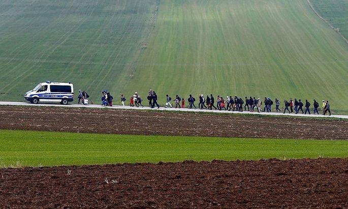 Die Polizei begleitet Flüchtlinge kurz nach dem Grenzübertritt nach Deutschland zur nächsten Unterkunft.