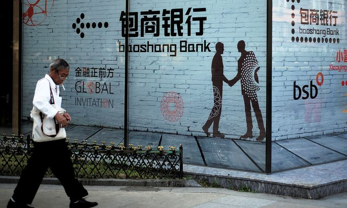 FILE PHOTO: Man walks past a building with an advertisement of Baoshang Bank in Beijing