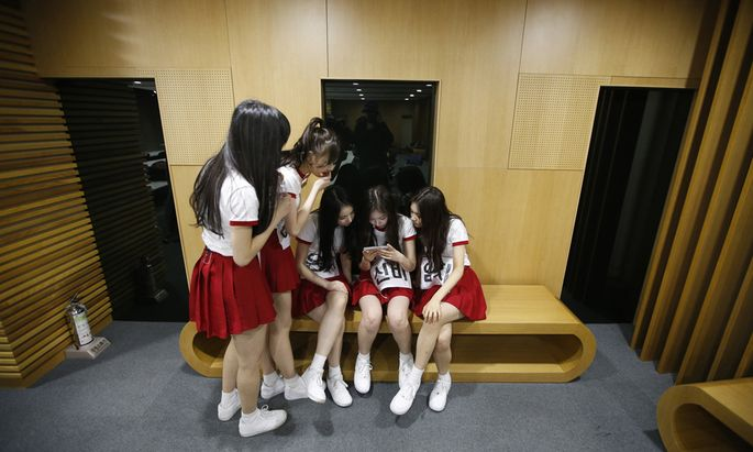 Members of South Korean girl group GFriend watch a recording of their stage performance during a dress rehearsal for The Show in Seoul