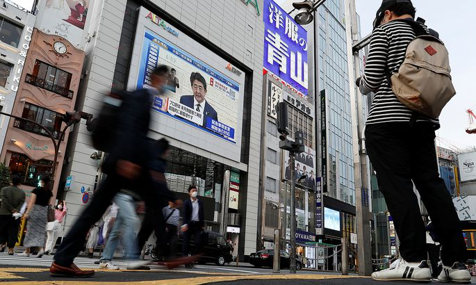 A large screen on a building shows live broadcast of Japan's Prime Minister Shinzo Abe's news conference at Shinjuku district in Tokyo