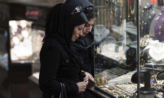 Women look at jewellery at a shop window in a bazaar in northern Tehran