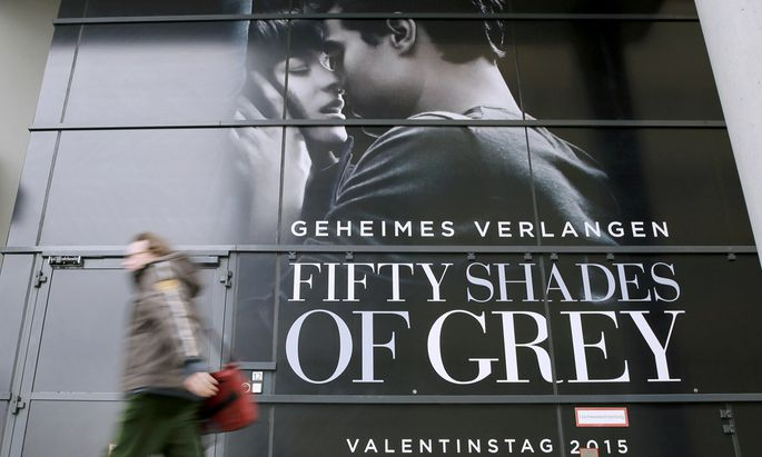 A pedestrian walks past advertisment for film ´Fifty Shades of Grey´ in Berlin